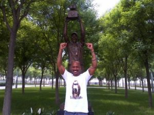 Marbury in posa davanti alla statua che lo omaggia.